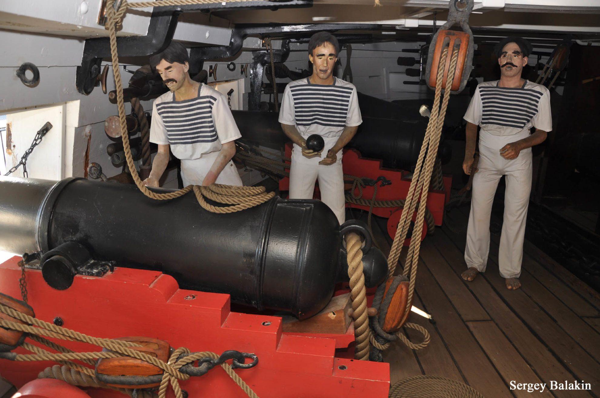 Комендоры 18-фунтового орудия в рубашках с горизонтальными полосами.