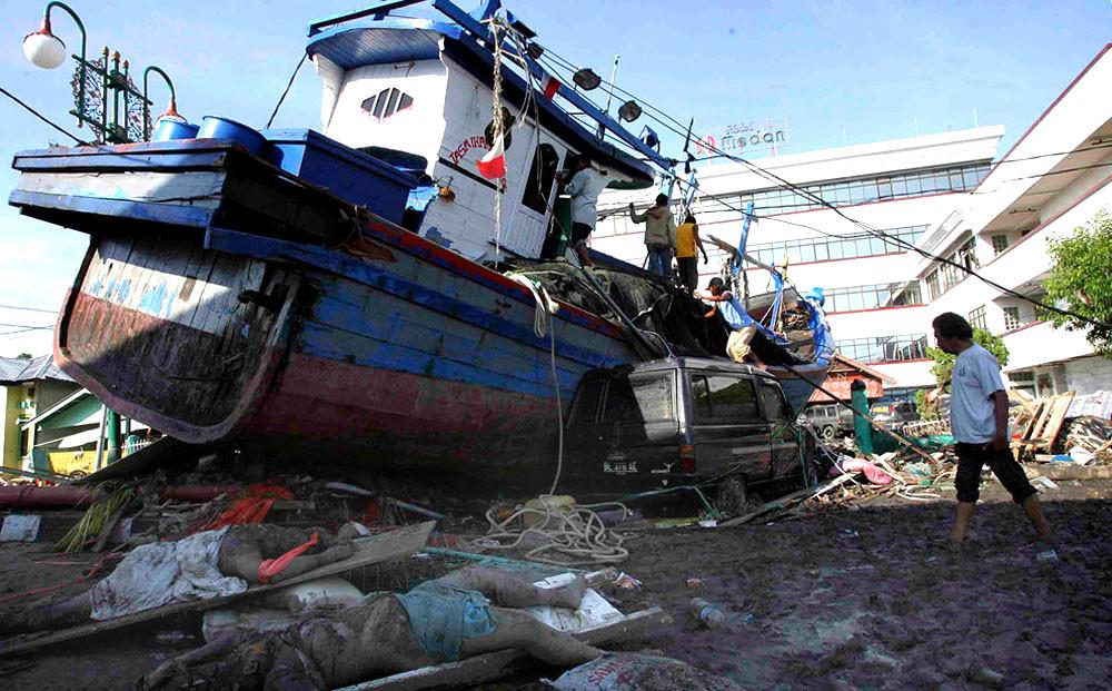 Индонезийский город Банда Ачех после цунами: выброшенный на берег рыболовный катер и тела погибших местных жителей на переднем плане, 28 декабря 2004 г.