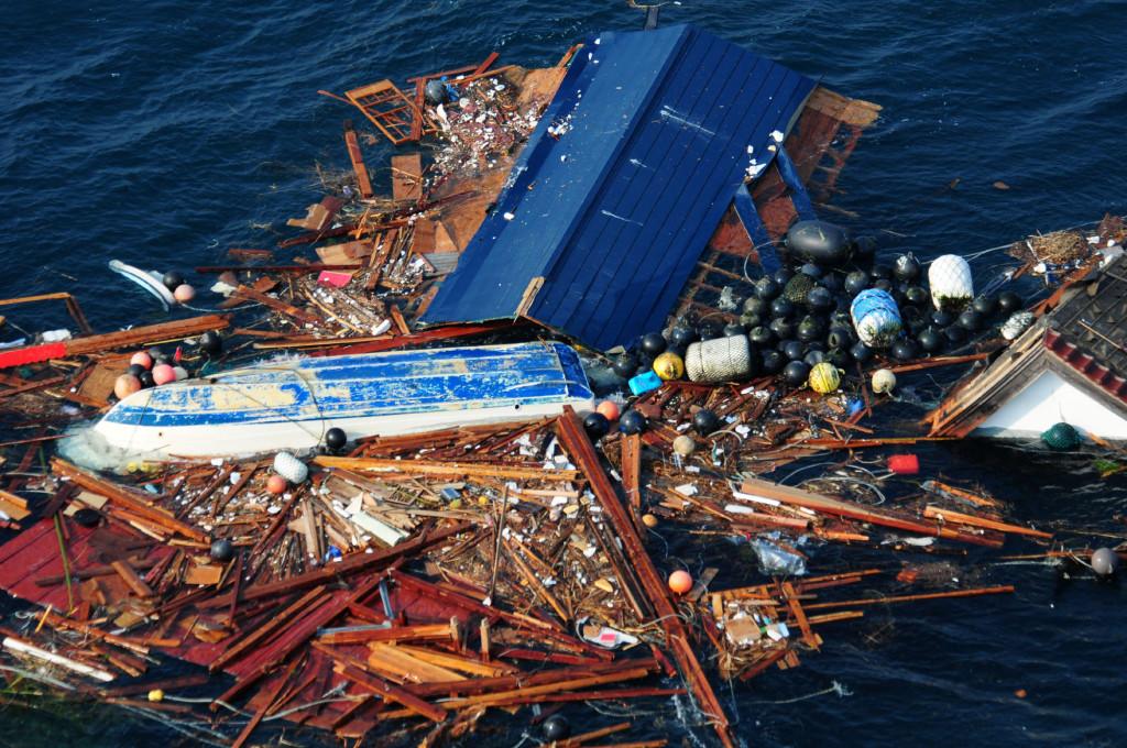 Смытые в океан обломки, мусор, перевёрнутая лодка…Снимок с американского патрульного самолёта, 11 марта 2011 г.
