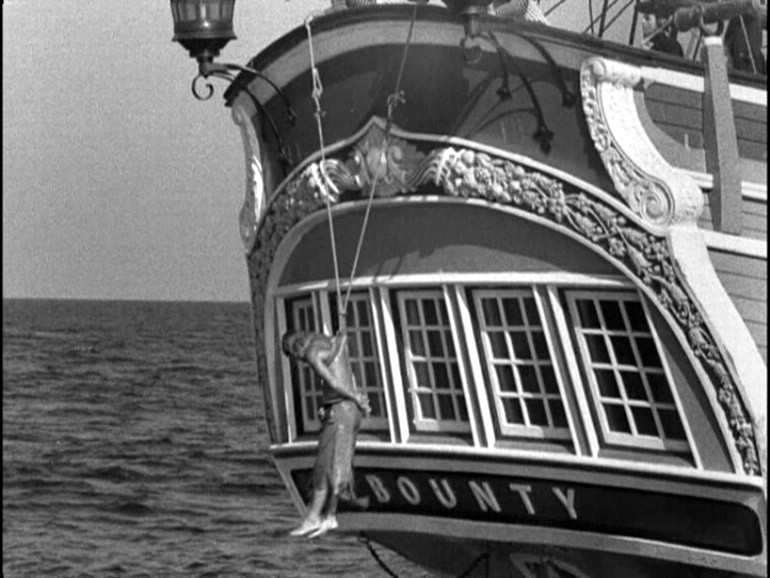 Ещё один кадр из художественного фильма - обладателя Оскара «Mutiny on the Bounty». Одного из членов экипажа «Баунти» подвергают принудительному «купанию». Именно жестокое обращение капитана Блая с командой своего судна стало причиной знаменитого мятежа.
