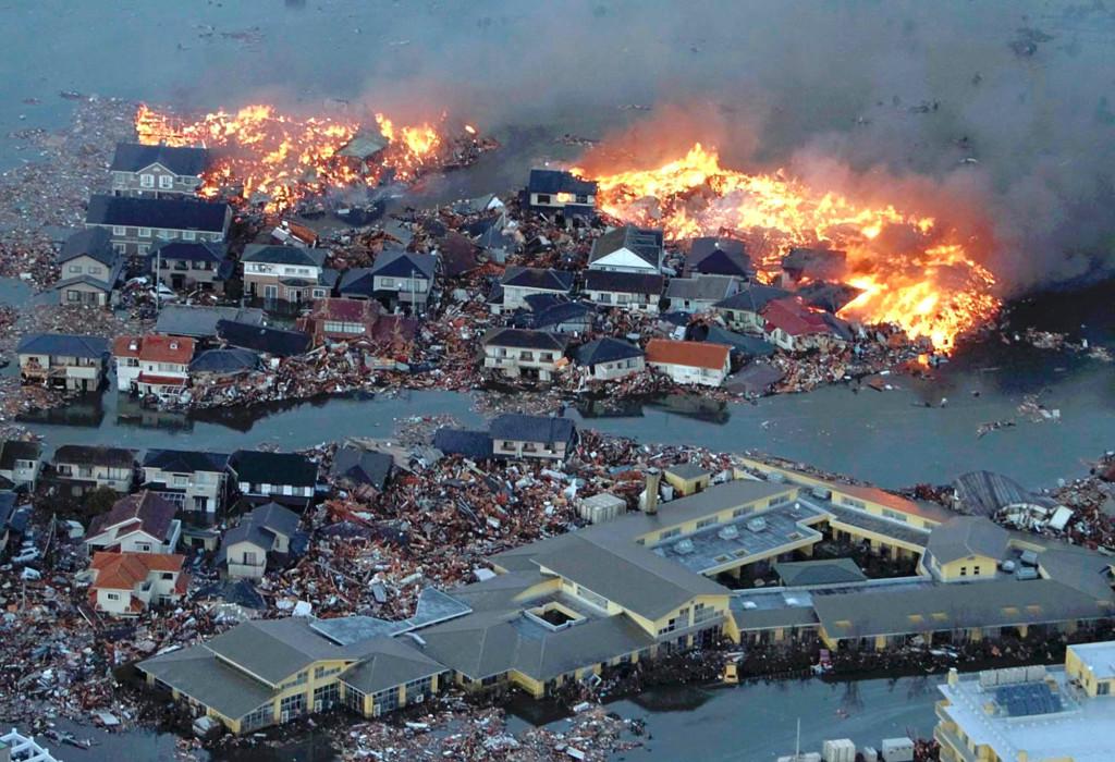 Houses swept out to sea burn following a tsunami and earthquake in Natori