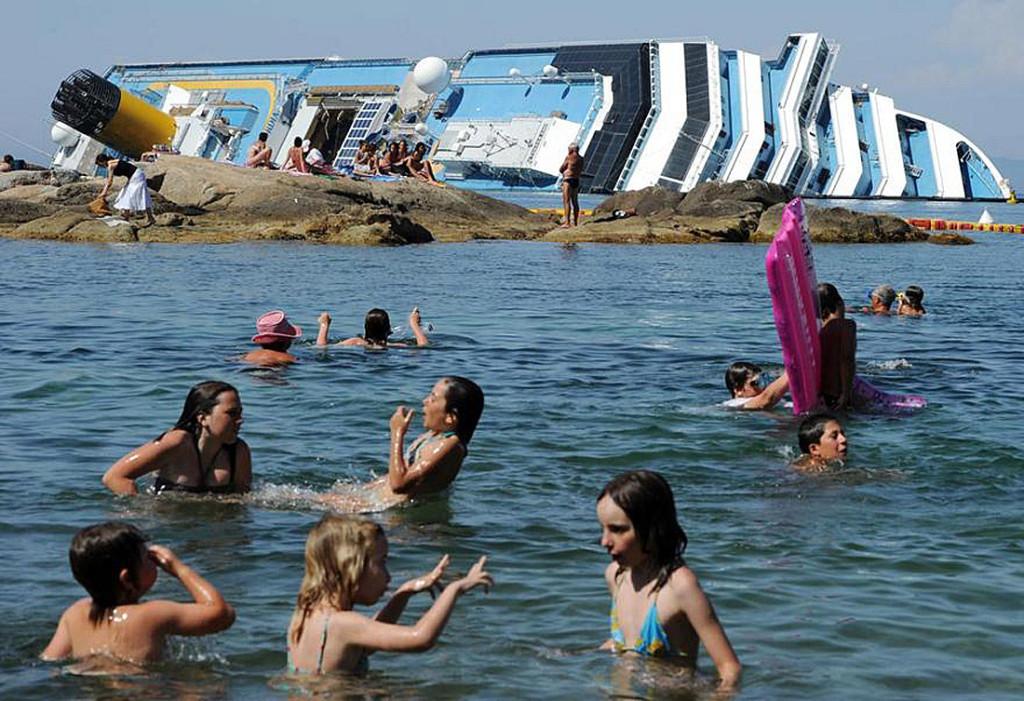 Turisti fanno il bagno di fronte alla Costa Concordia