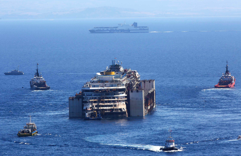 A Grimaldi lines ship sails in front of the cruise liner Costa Concordia during the refloat operation maneuvers at Giglio Island